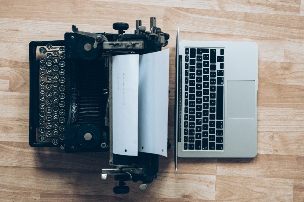 An old typewriter back-to-back with a modern laptop. Modern vs old marketing