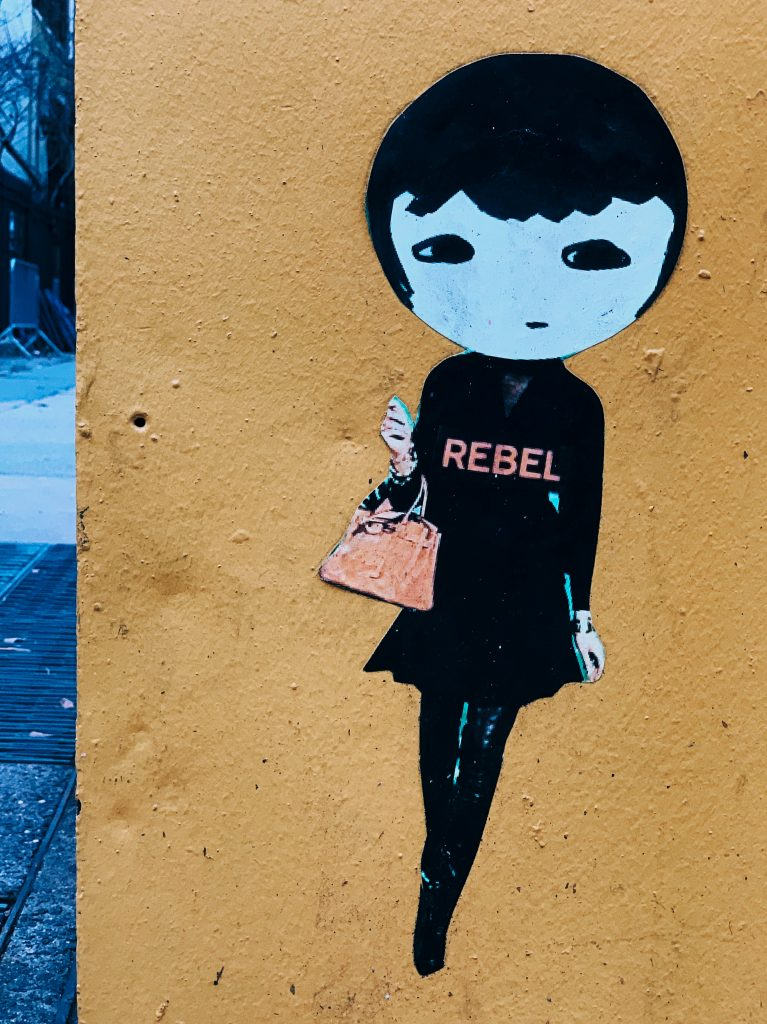 Image of a girl on a wall wearing a t-shirt that says REBEL.