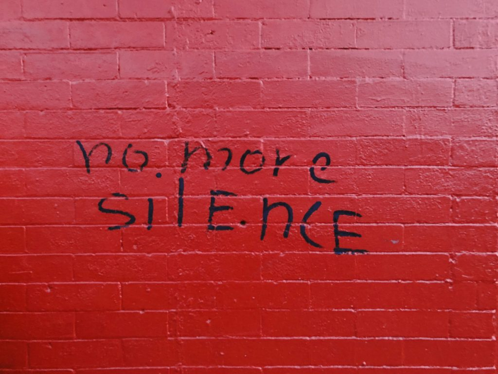 "Red brick wall. Has the words ""no more silence"" written in graffiti on it in black."