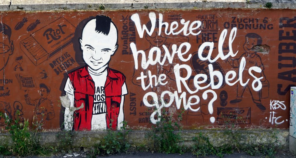 "Picture of graffiti on a wall. It reads ""Where have all the rebels gone?"""